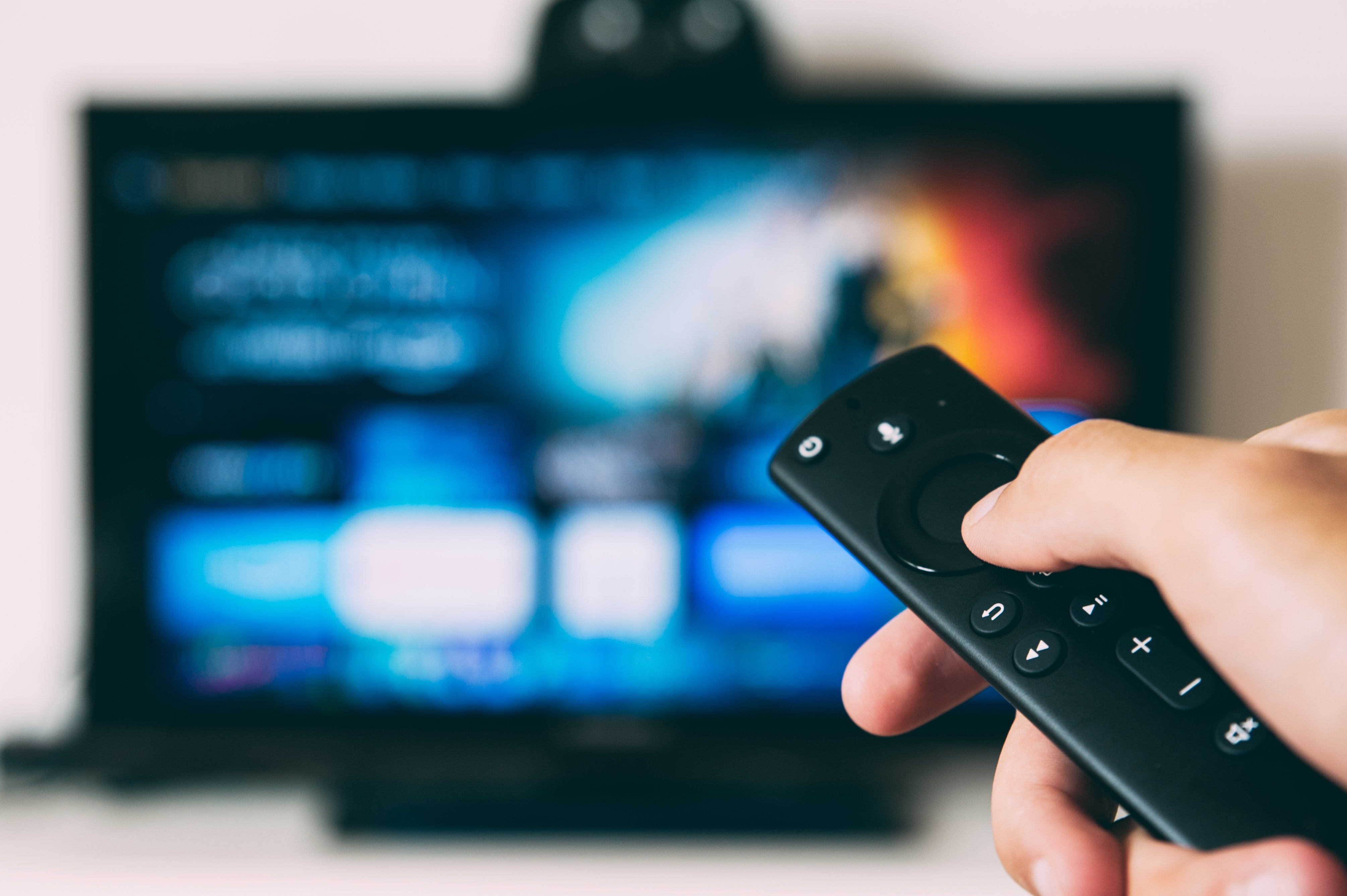 A person holding a television remote about to watch live entertainment from home
