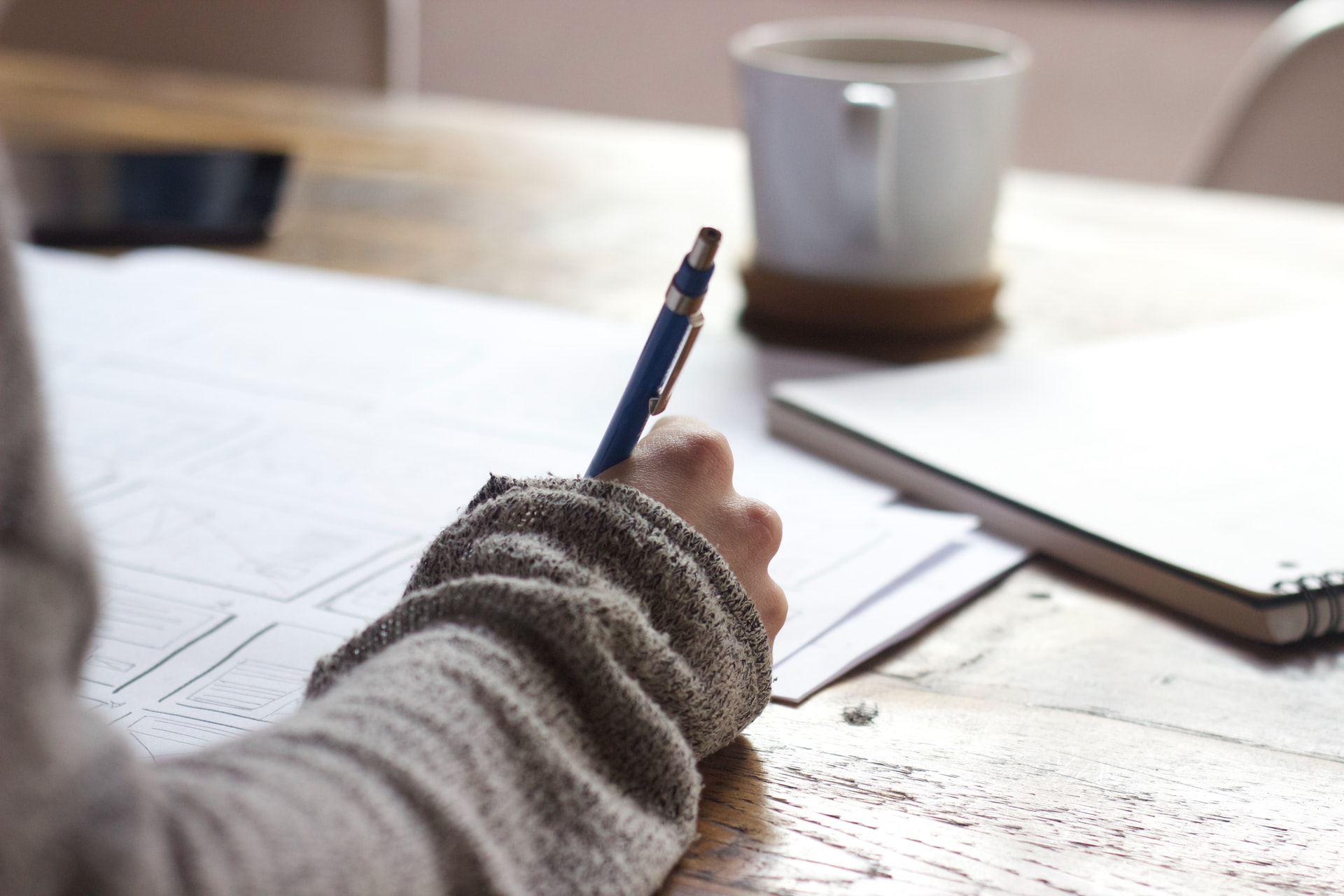 A person writing with a pen with a cup of coffee on their desk